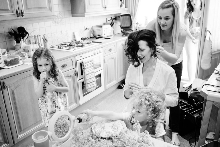 bride getting hair done in kitchen