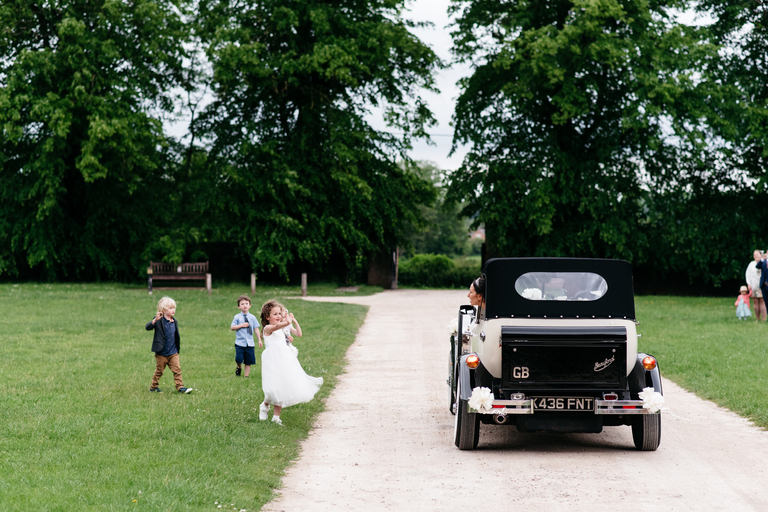 kids waving the wedding car off