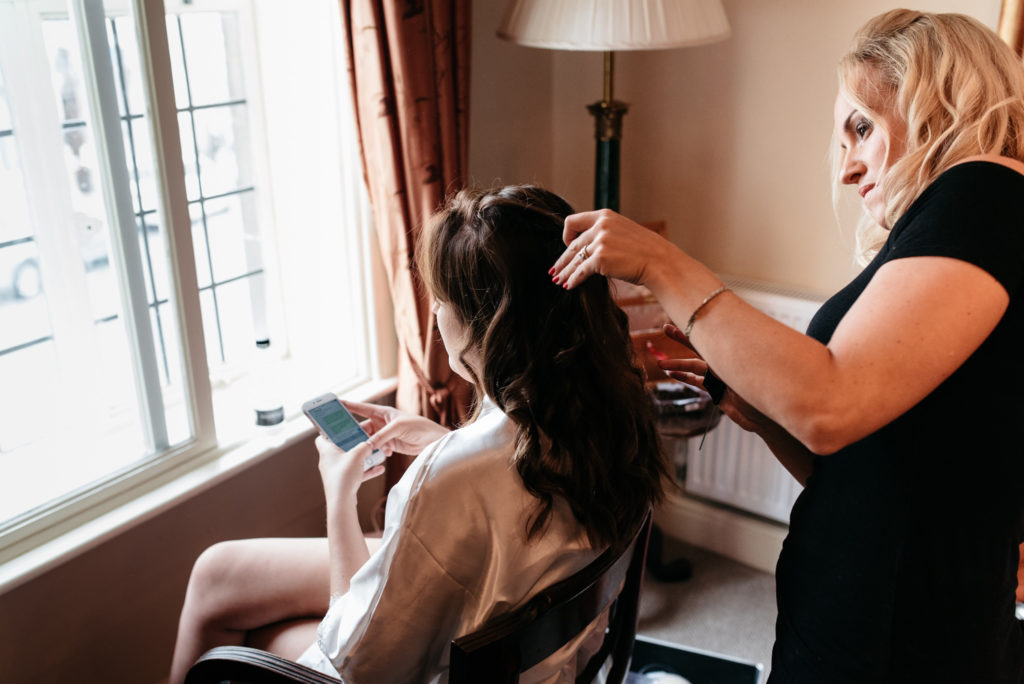 bride on her phone while getting her hair done