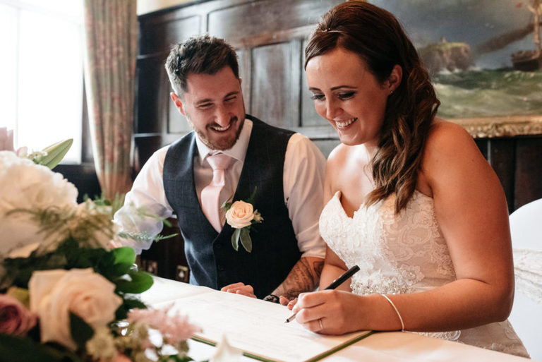smiling and signing the register