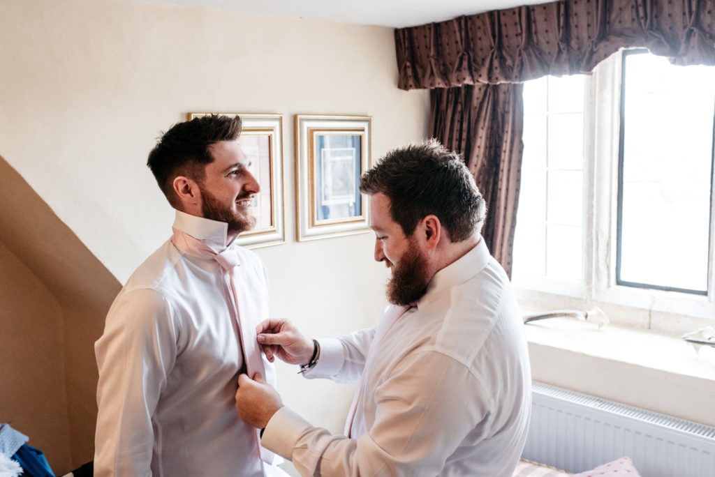 grooms brother helps with his tie