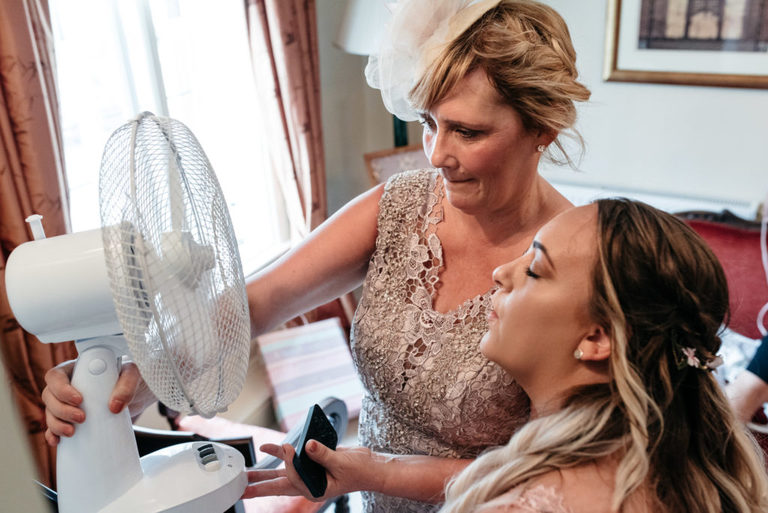 mother of the bride and bridesmaid cool down with fan