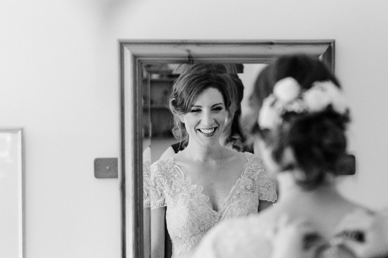 smiling bride looking at herself in the mirror