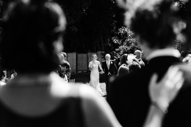 bride walking down the aisle in her parent's garden