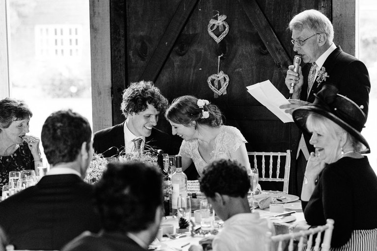 couple laughing during father's speech