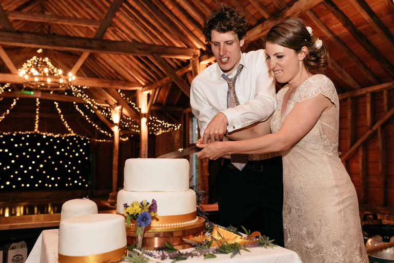 bride and groom cutting the cake with funny faces