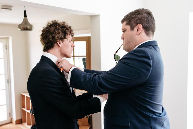 best man fixes grooms collar