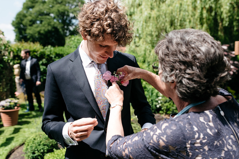 bride's mum fits groom's button hole