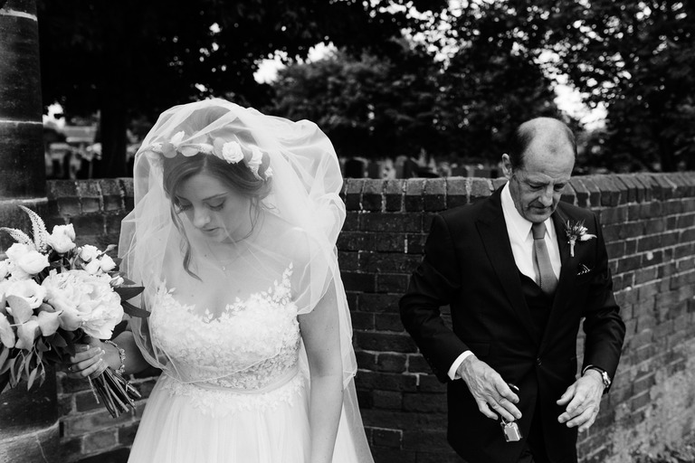 bride with her dad at the church gates