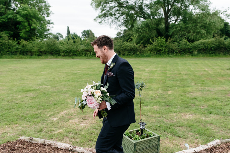 groom with brides bouquet