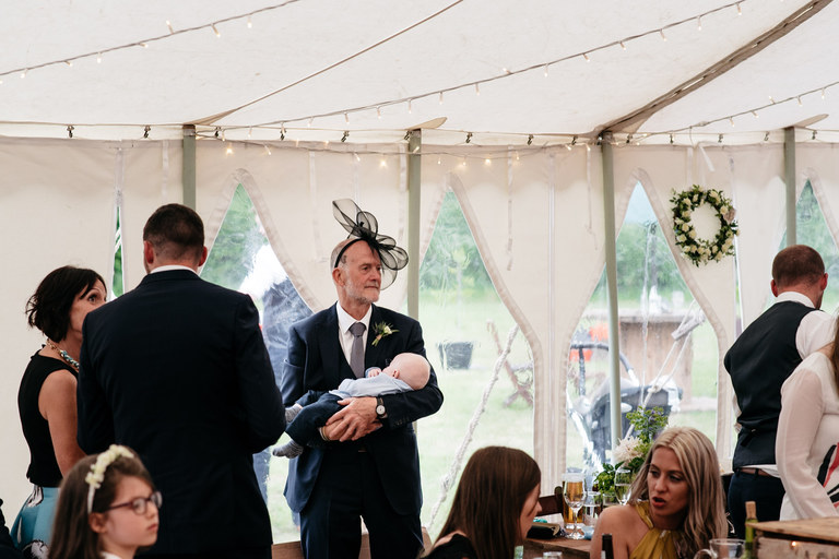 father of the groom holding a baby
