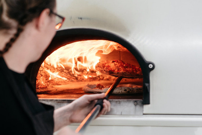 pizza being put in the oven
