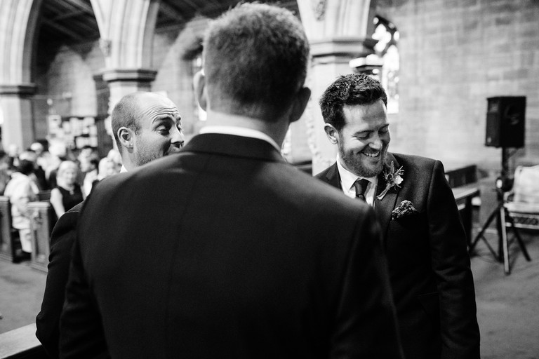 groom laughing at the altar with best man