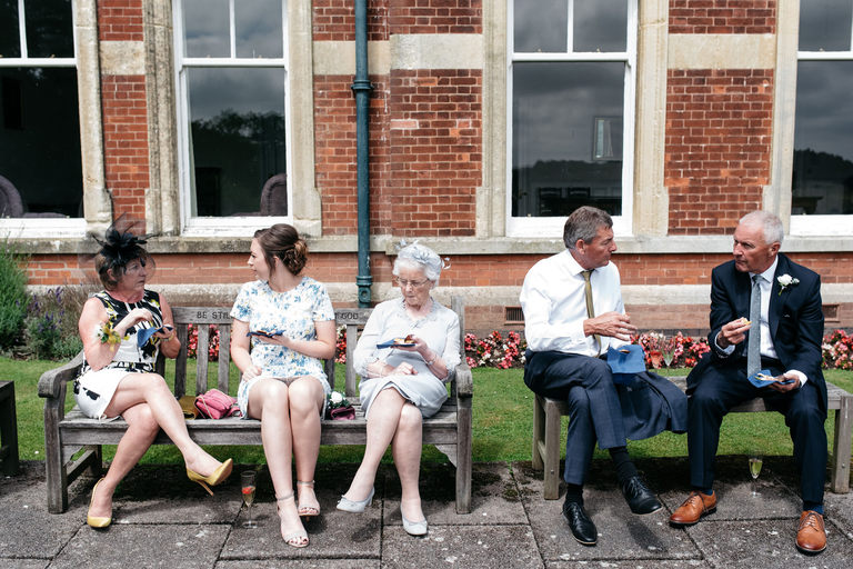 guests sitting on benches in the sun