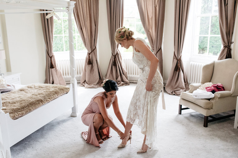 bridesmaid helps bride put on her shoes