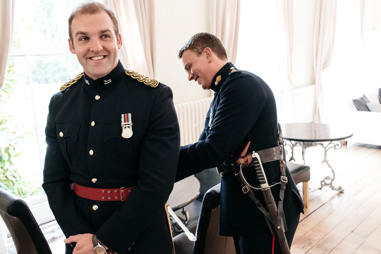 groom gets into his military uniform