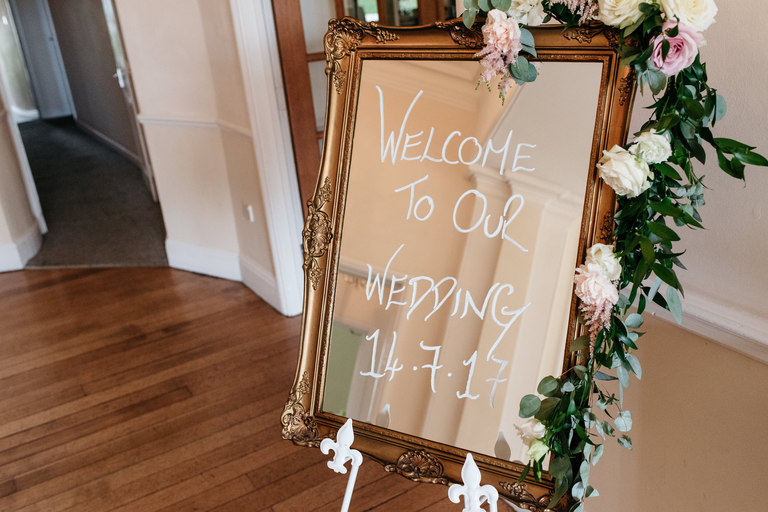 welcome to wedding sign written on mirror