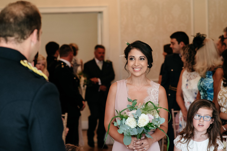 smiling bridesmaid walks down the aisle