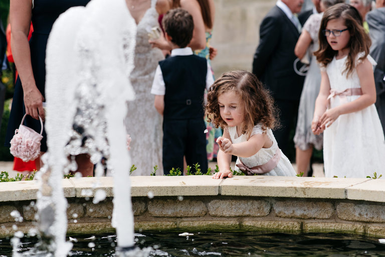 little girl throwing stones into the fountain