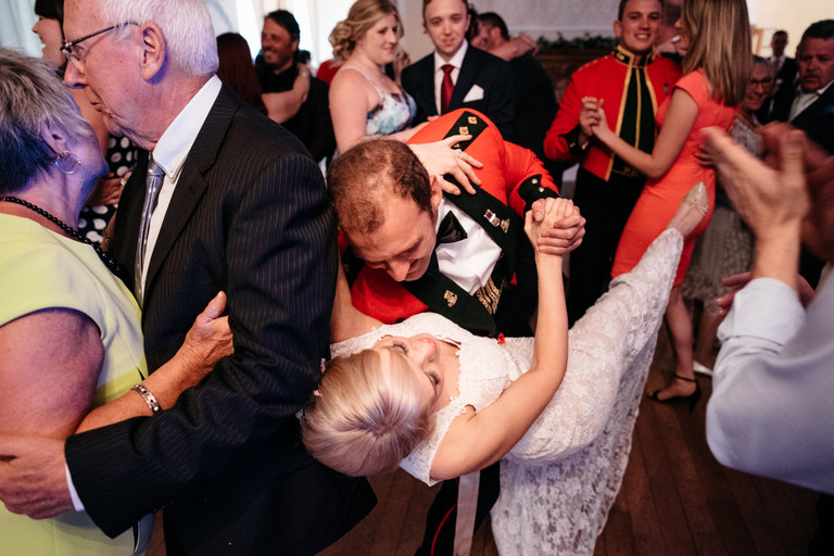 groom dips bride while dancing