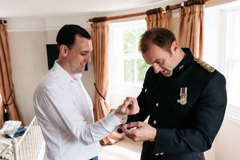 groom helping best man with cufflinks