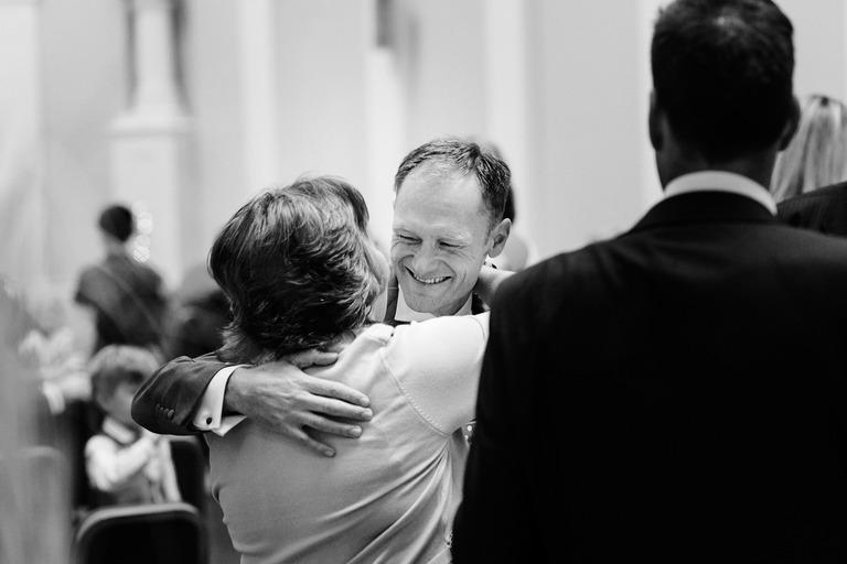 smiling groom hugging guests