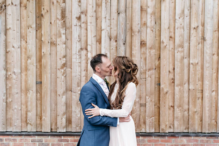 relaxed wedding portrait in front of natural wood