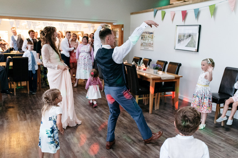 groom showing silly dance moves to kids