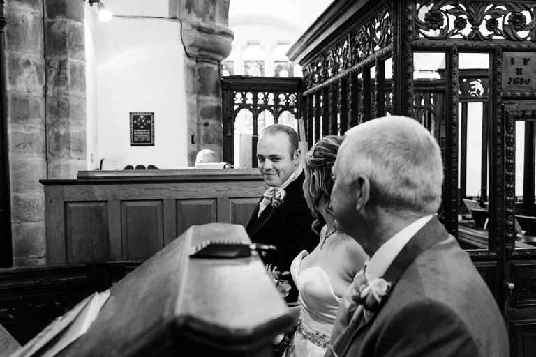 groom exchanges a smile with his bride