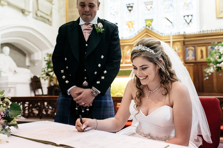 couple signing the register in church