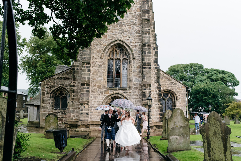 guests leaving church with umbrellas