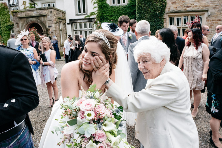 grandma puts a loving hand on her granddaughter's face