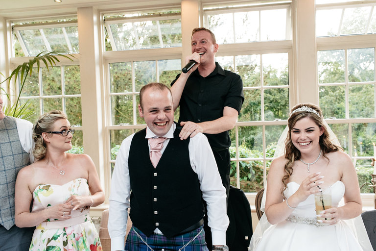 singing waiter with bride and groom