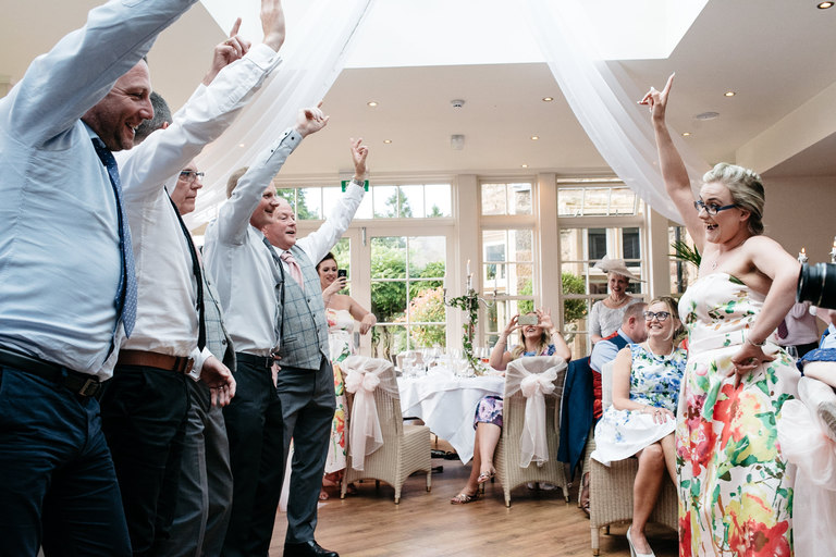 bridesmaid teaches group of men to dance