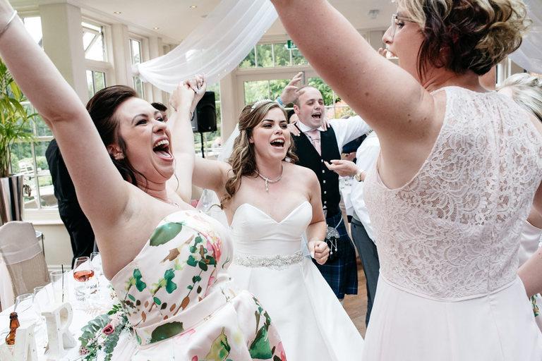happy bride dances with friends