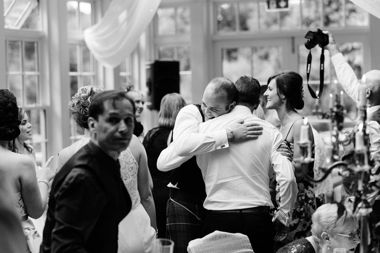 groom smiling and hugging a guest