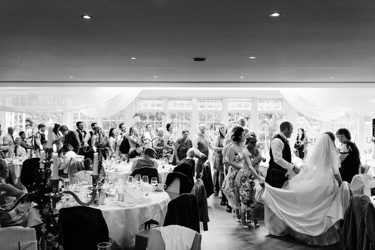 bride and guests dancing the conga