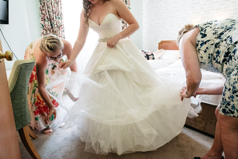 mother and bride helping with wedding dress