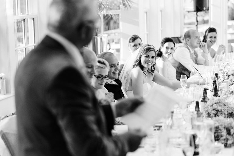 bride smiling up at her father during his speech