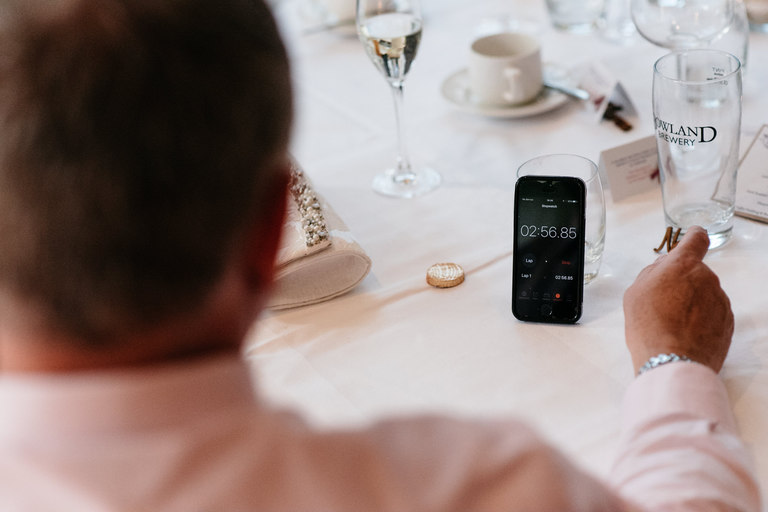 guest timing the speeches on their phone