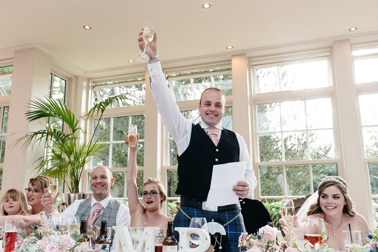 groom raising a glass in toast