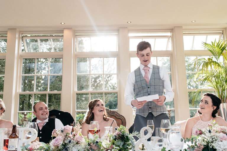 couple laughing during best man's speech