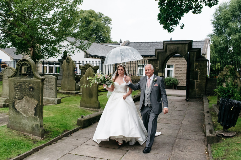 bride and father arriving at church with umbrella