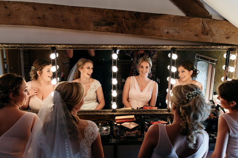 bride with bridesmaids at dressing table