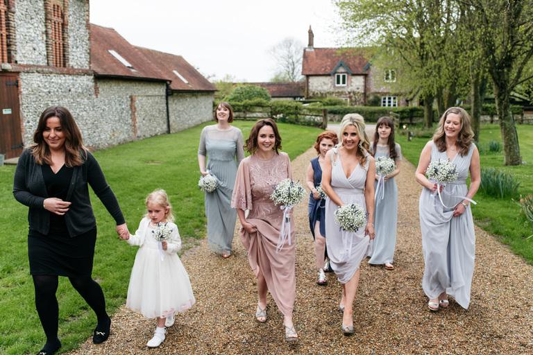 bridesmaids walking outside tithe barn