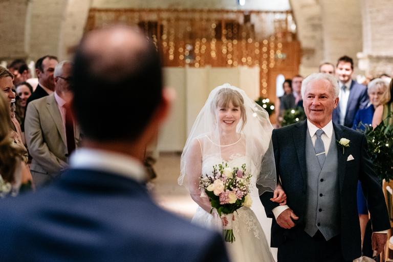 bride walking down aisle tithe barn