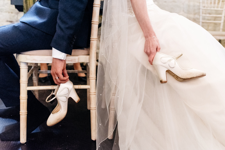 bride and groom holding wedding shoes