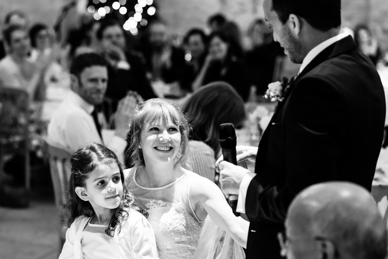 bride smiling at groom during speech