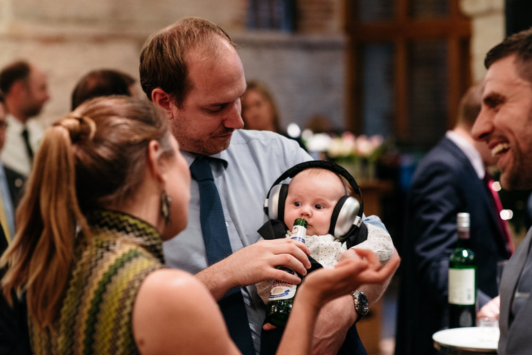 baby with ear protectors and beer