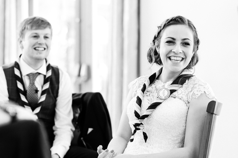 smiling bride and groom during speeches